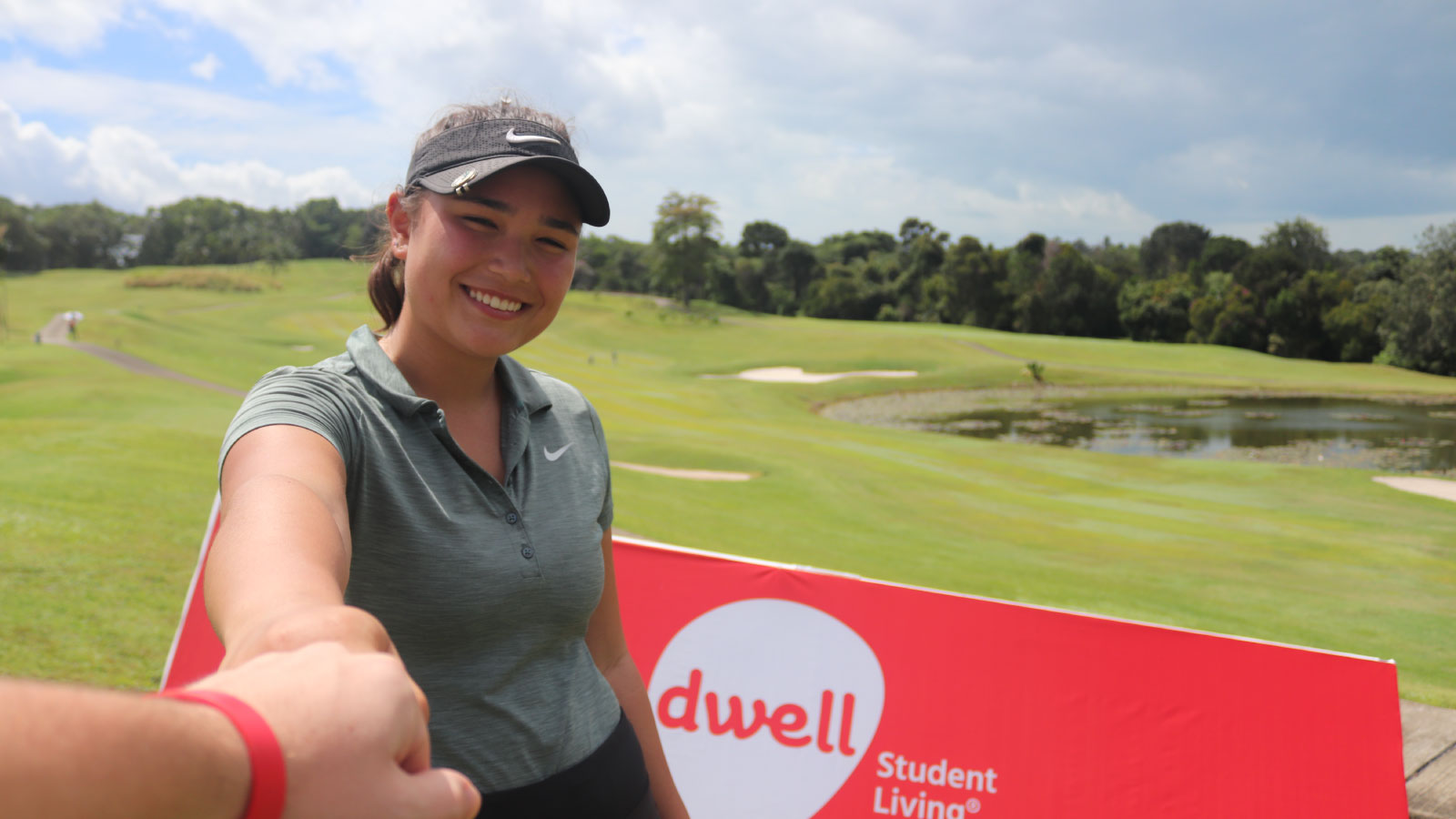 Camille Boyd, top-ranked player on the Junior Order of Merit Rankings 2017-2018, posing in front of dwell Student Living signage at Bintan Lagoon Resort